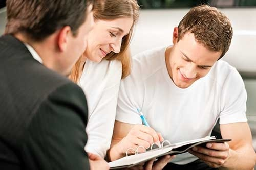 Couple signing purchase papers for car