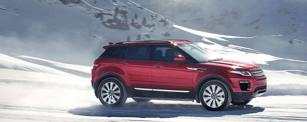 red 2019 range rover evoque in front of snowy mountain