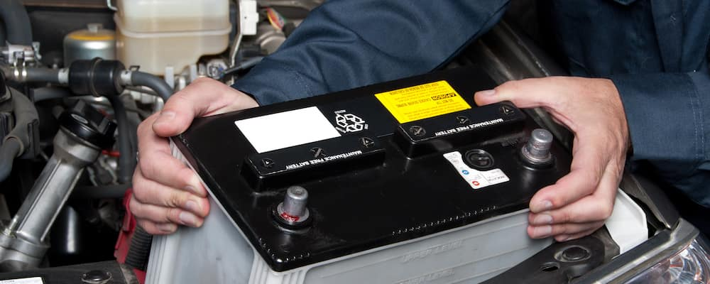 closeup of technician replacing car battery