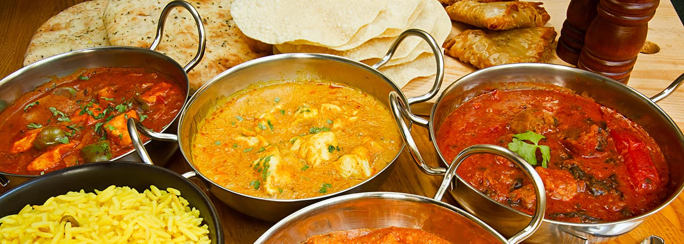 Selection of indian food with pilau rice, naan bread