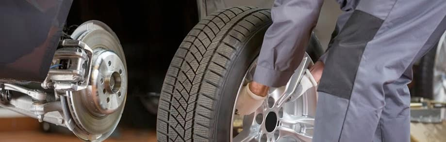 Mechanic Putting Tire on Car