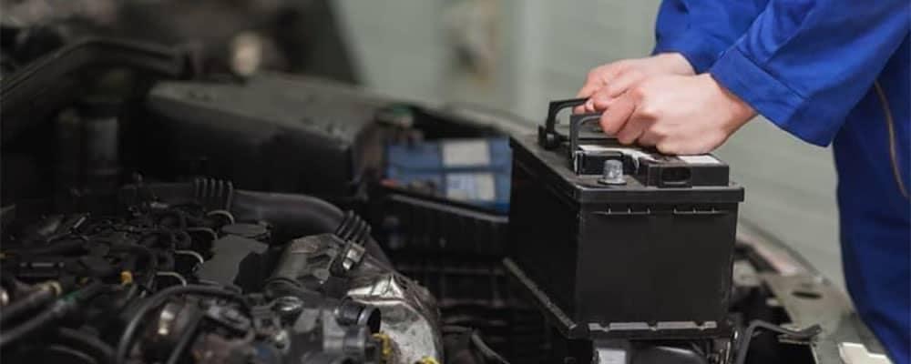 Mechanic removing car battery