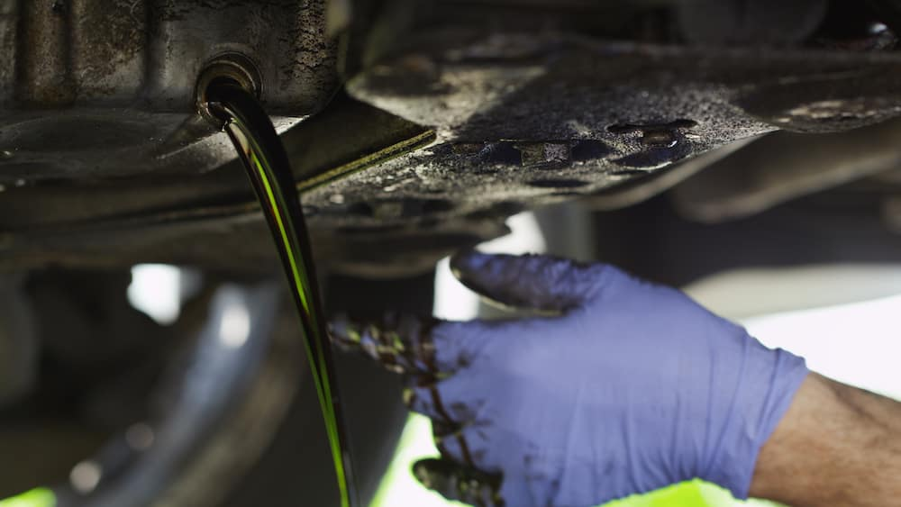 Blue Glove Hand Drains Dirty Oil from Under Car