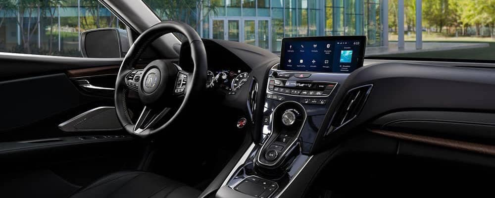 Acura RDX dashboard interior with trees and a building showing through the windshield