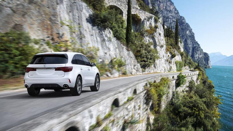 White MDX driving on a road on a mountainside next to a lake