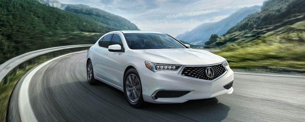 White Acura TLX driving on a winding road with green mountains in the background