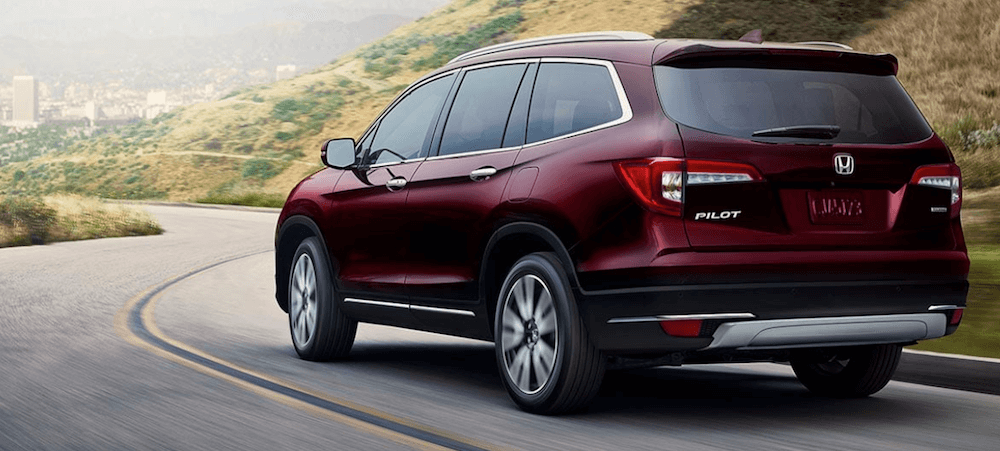 Red 2019 Honda Pilot driving on hilly road