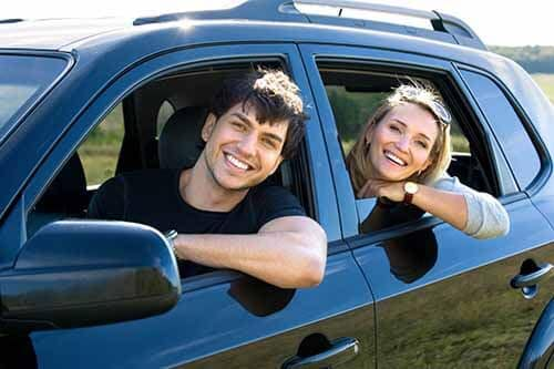 Happy young couple driving the car