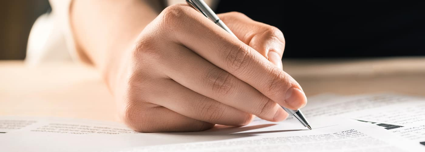 woman signing contract close up of hand pen and paper