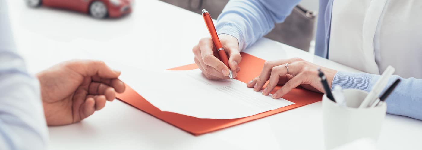 woman signing car insurance papers