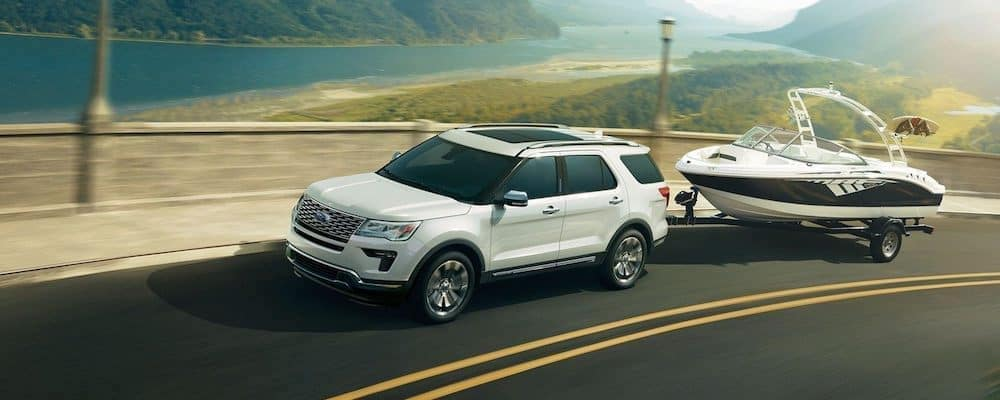 2019 ford explorer white exterior driving down road towing boat
