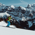 person skiing downhill in green jacket