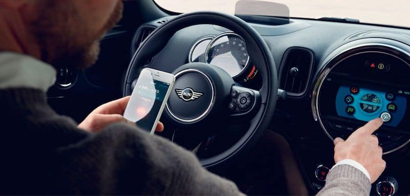 Man Configuring Smartphone to 2019 MINI Countryman Infotainment System