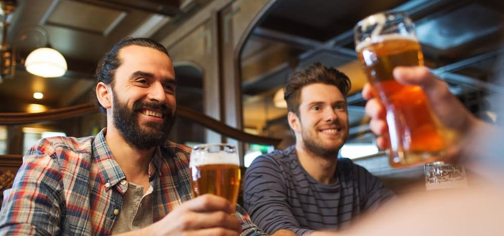 Two men drinking beer and smiling