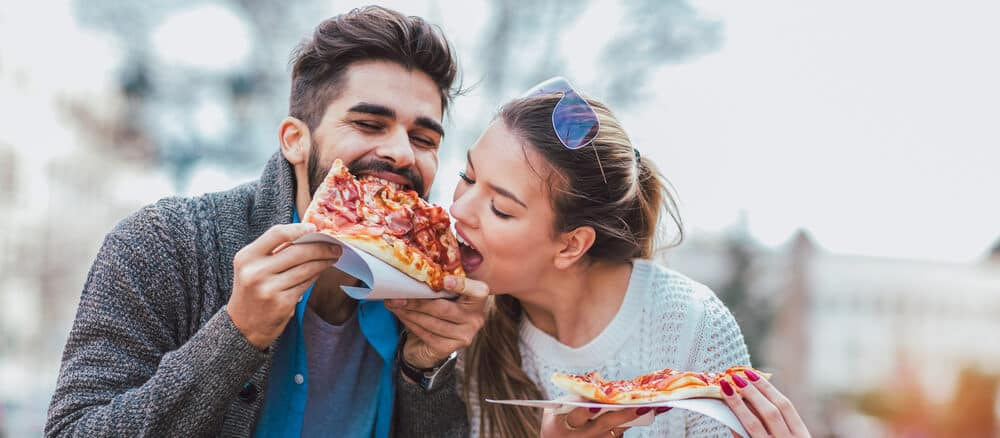 Couple eating pizza outdoors