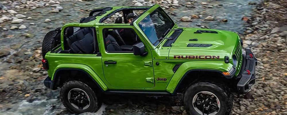 Green 2019 Jeep Wrangler crossing shallow water