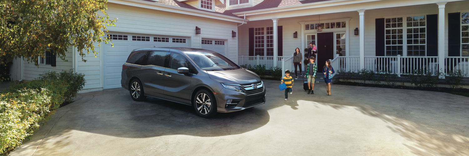 A Family Running To Their 2019 Honda Odyssey In The Driveway