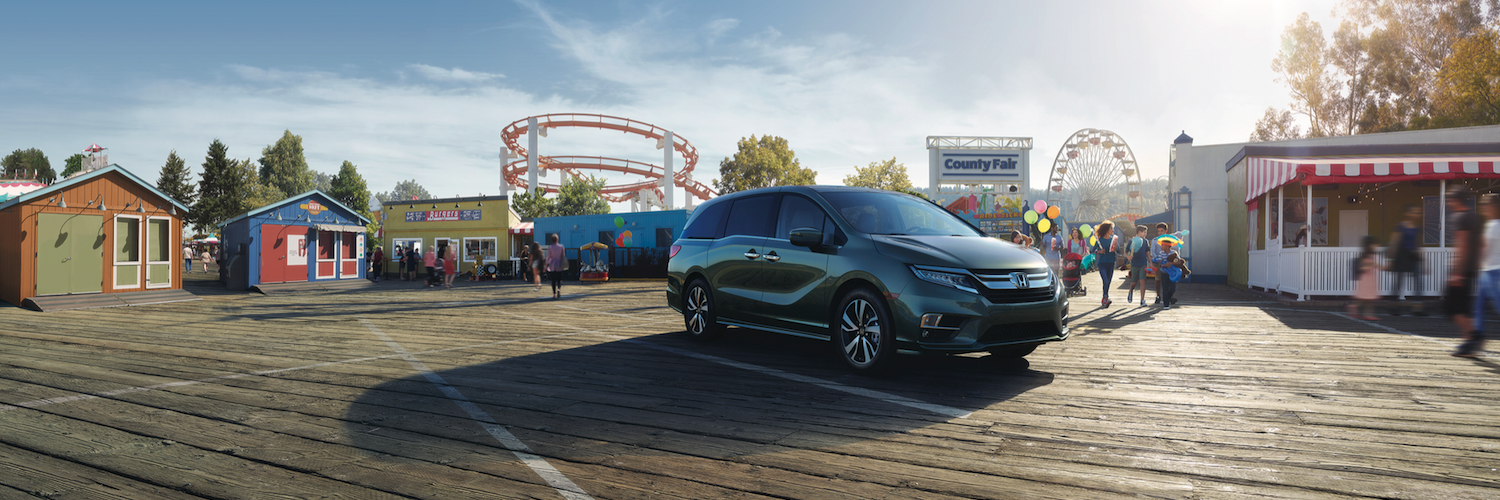 A 2019 Honda Odyssey parked just outside the entrance to a fair
