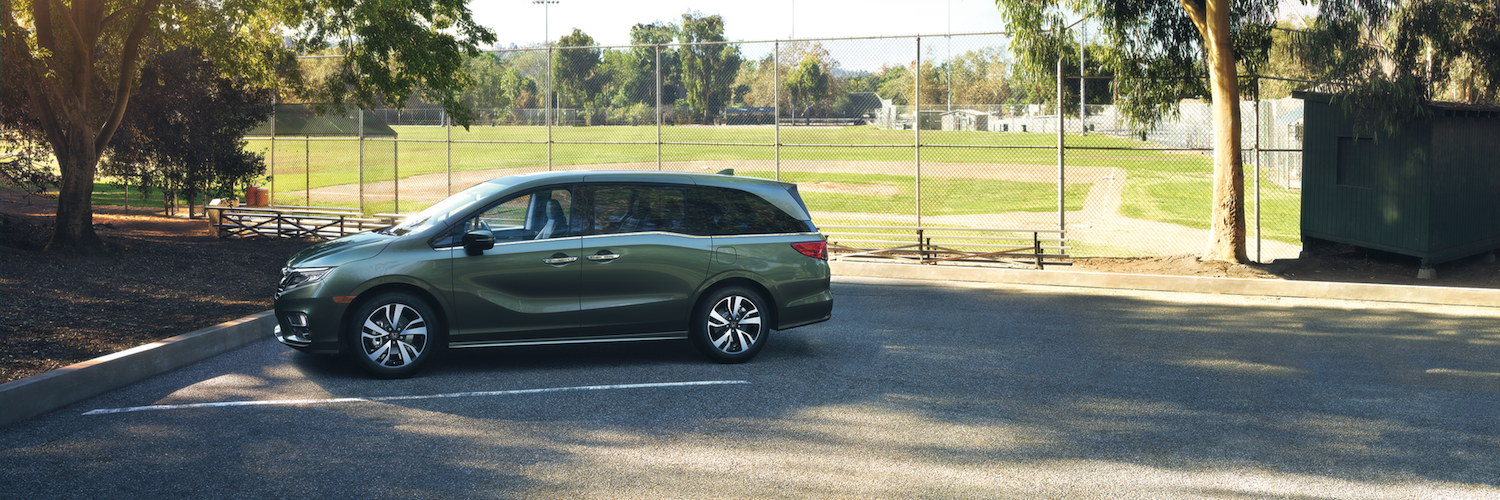 A green Honda Odyssey parked in a parking lot by a field