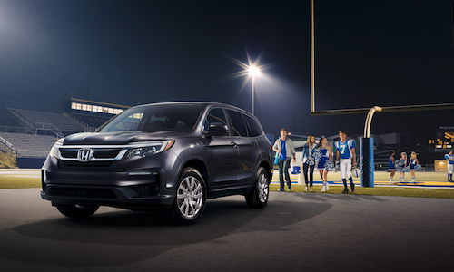 A family at a highschool footbal game walking to their 2019 Honda Pilot