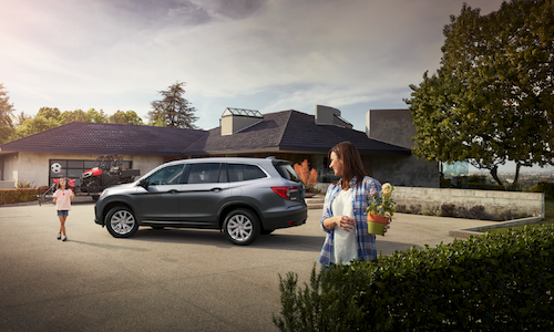 A mom and her daughter in the driveway by their 2019 Honda Pilot