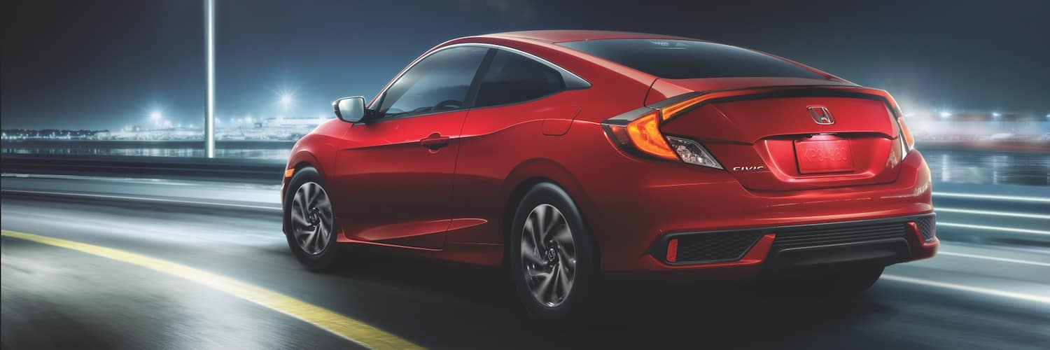 A red 2019 Honda Civic driving around a bend