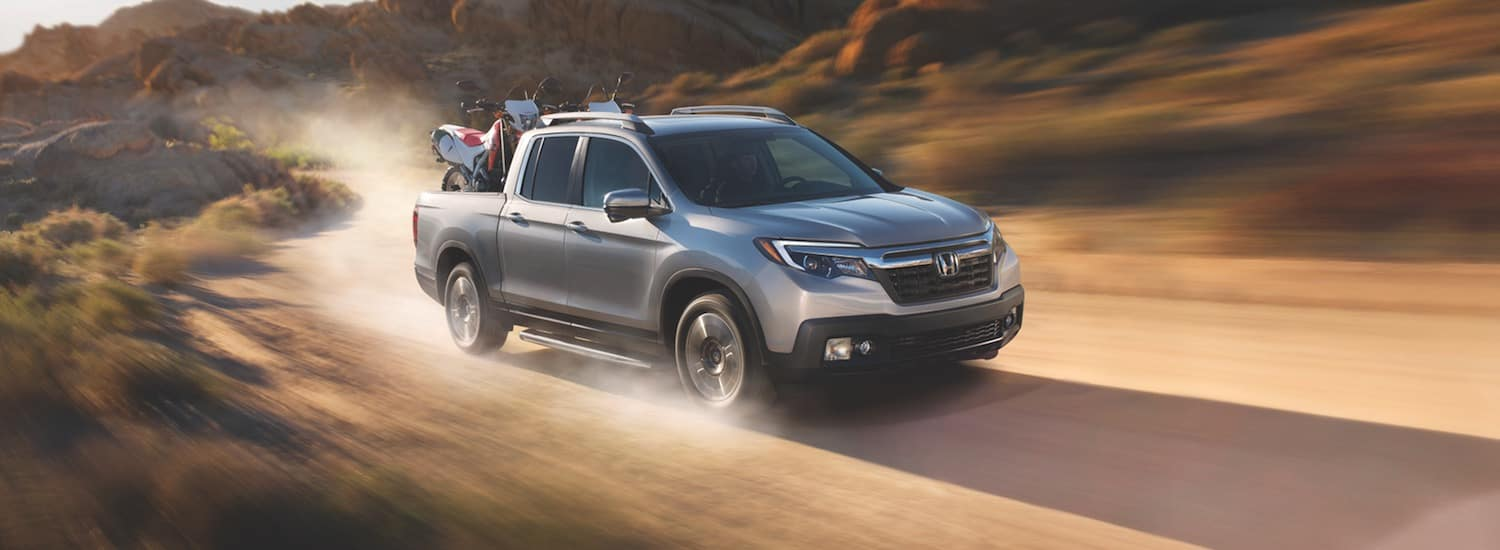 A 2019 Honda Ridgeline carrying two motocycles down a dirt path
