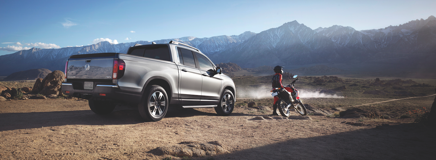 A 2019 Honda Ridgeline parked by the mountains with a motorcyclist