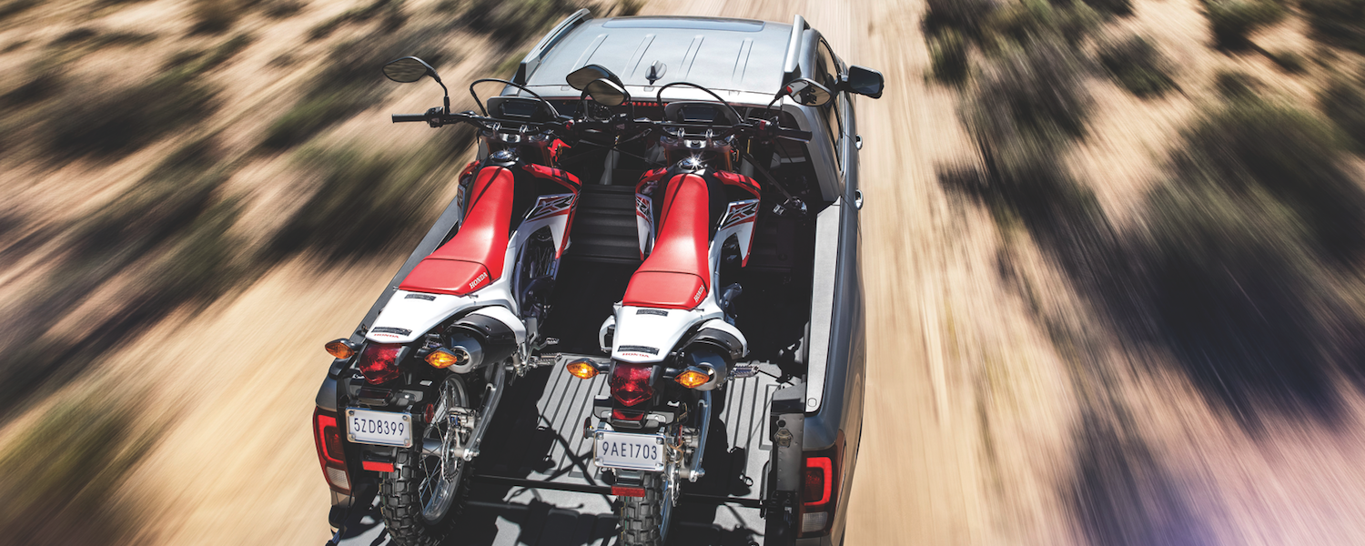 A 2019 Honda Ridgeline carrying two motorcycles in the desert