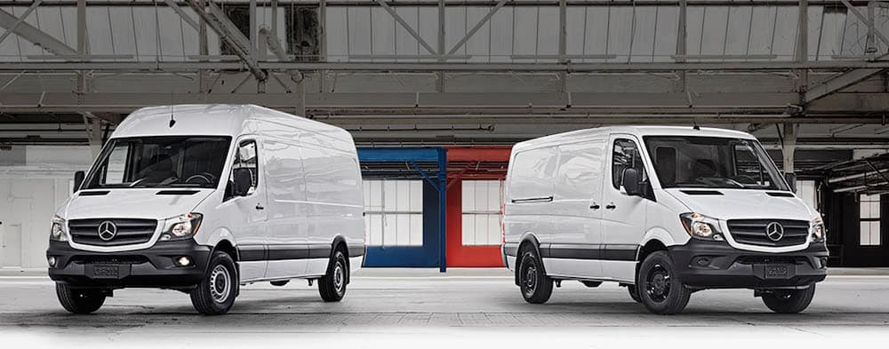 Two white sprinter vans parked next to each other in a warehouse