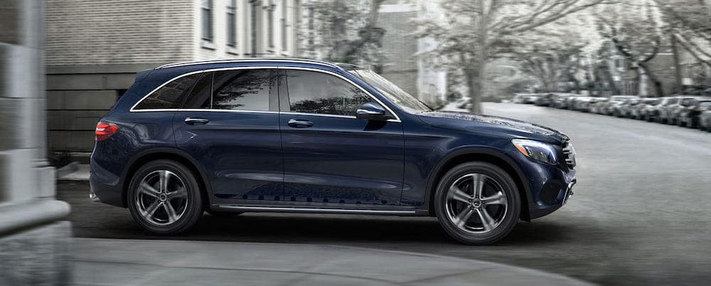 Blue GLC SUV parked in front a gray building