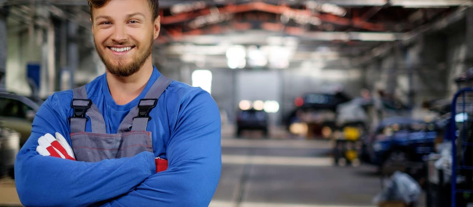 Cheerful serviceman in a car workshop