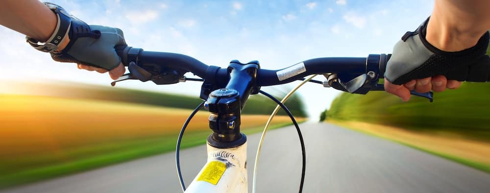 Hands in gloves holding handlebar of a bicycle. Motion blurred asphalt road