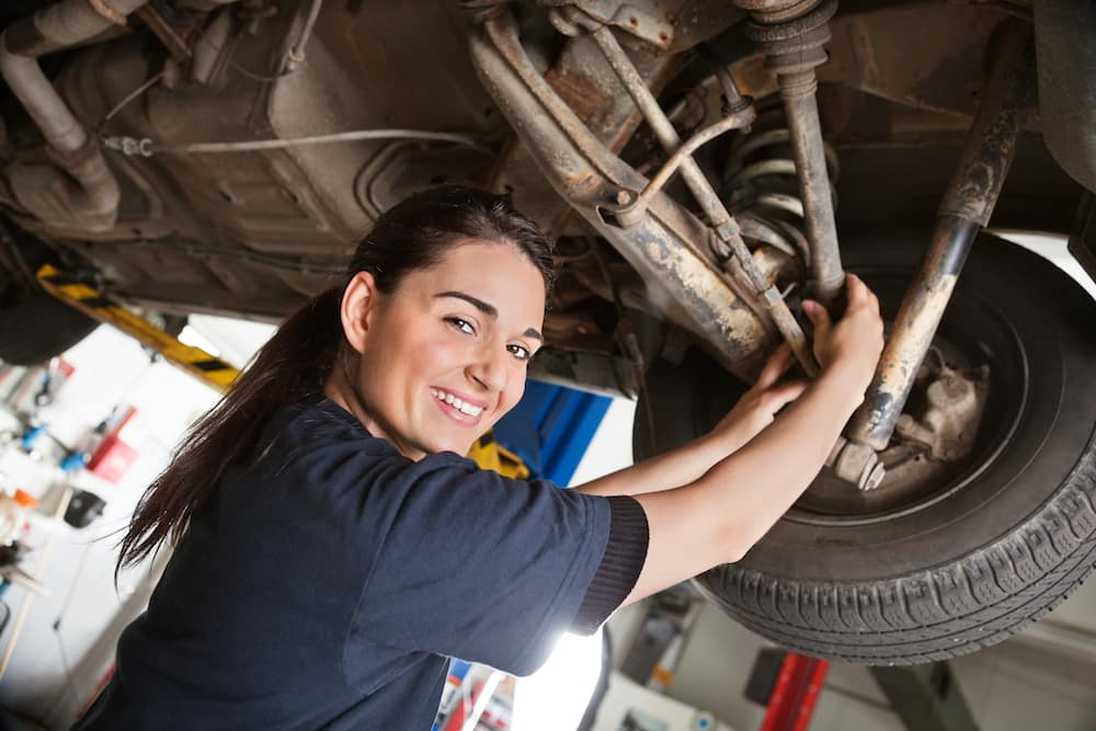 Female mechanic working on a car and smiling
