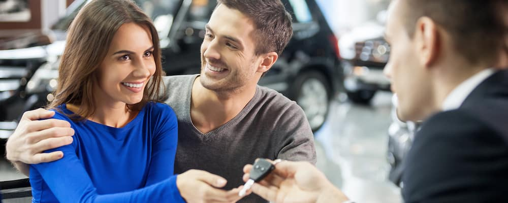 couple getting keys from salesman