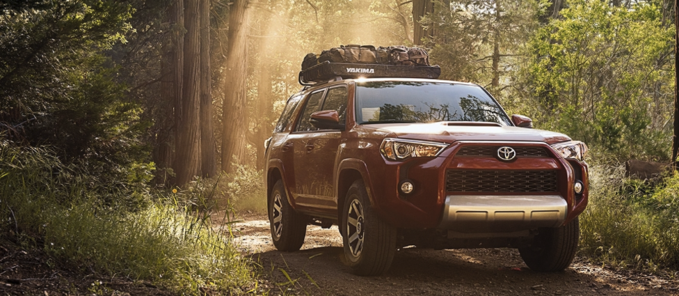 A red 2017 Toyota 4Runner driving through the woods.