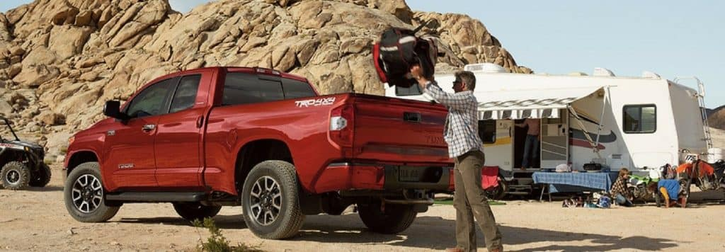 A man loading something into the back of a 2018 Toyota Tundra