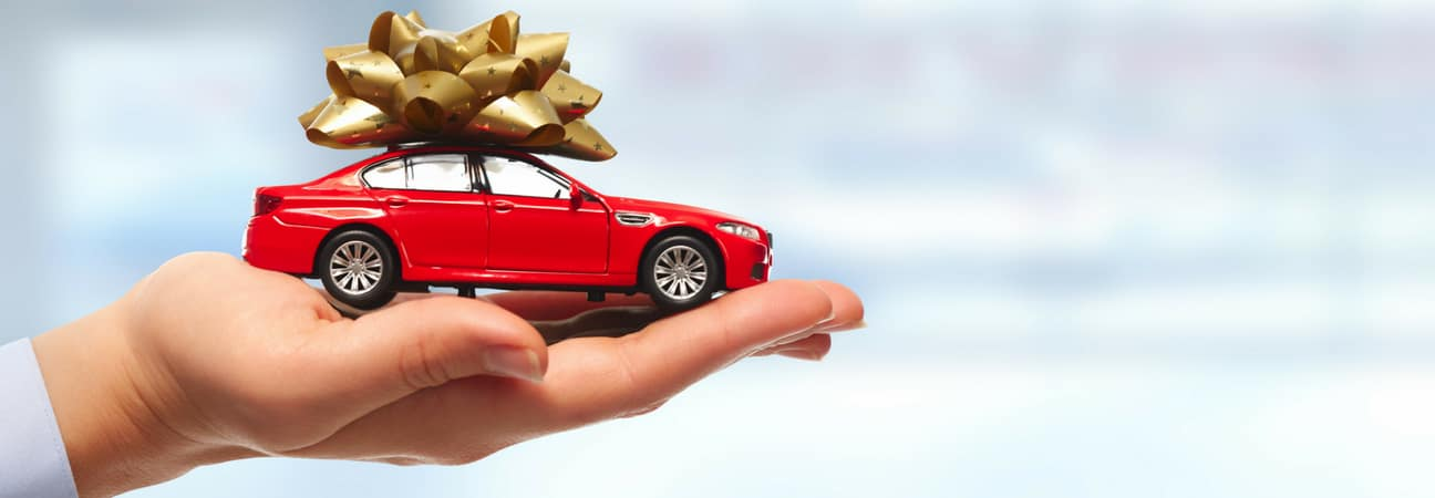 Hand holding red toy car with gold bow