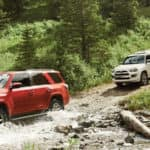 Red 2018 Toyota 4Runner and white 2018 Toyota 4Runner fording a stream