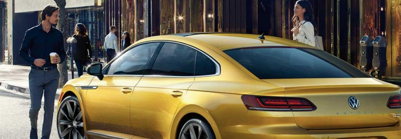 A man and woman leaving a coffee shop to get into a 2019 Volkswagen Arteon in gold.