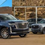 Two 2021 Cadillac Escalades parked outside building