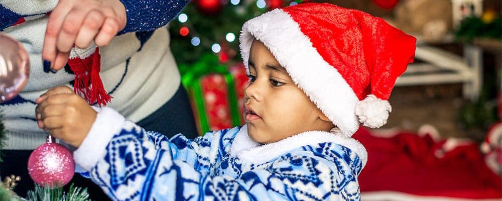 Little boy in Santa hat hanging an ornament