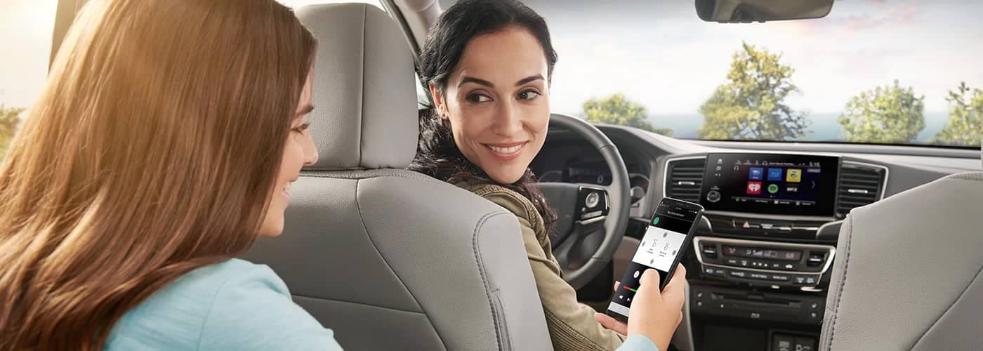 Mom and Daughter hooking phone to Honda Pilot