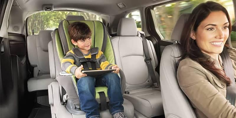 Young child on ipad in rear of Honda Odyssey